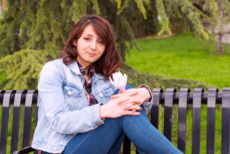 Härlig kvinna som sitter på en bänk arkivfoton