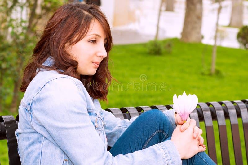 Härlig kvinna som sitter på en bänk fotografering för bildbyråer