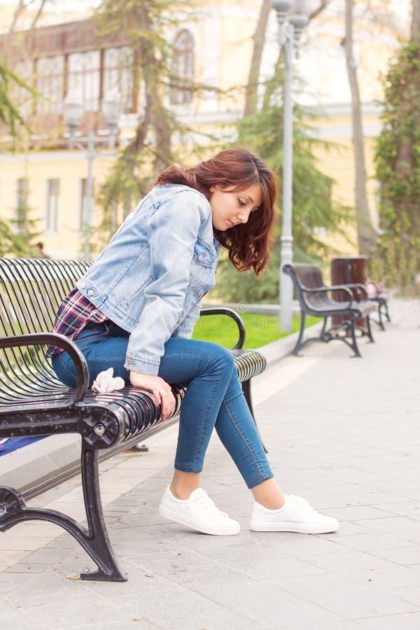 Härlig kvinna som sitter på en bänk royaltyfri fotografi