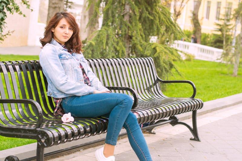 Härlig kvinna som sitter på en bänk arkivbild