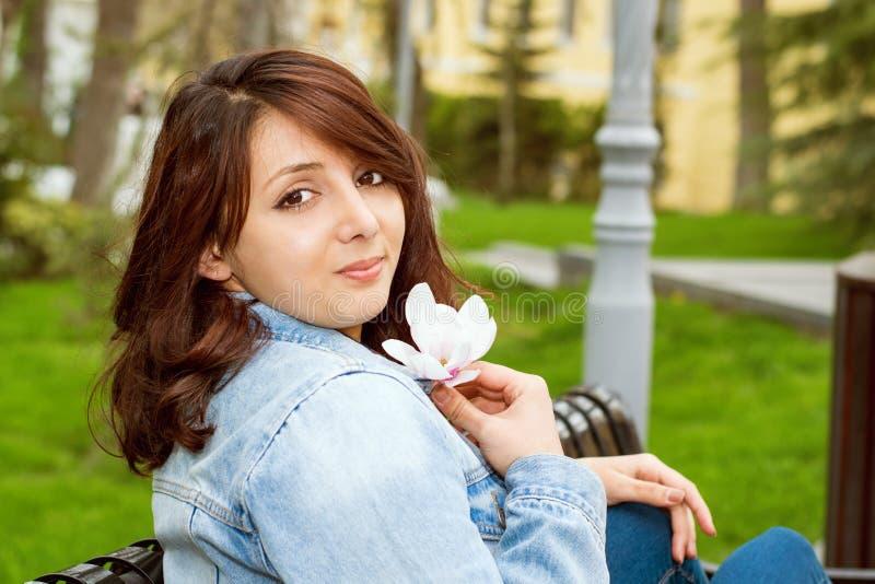 Härlig kvinna som sitter på en bänk arkivfoto