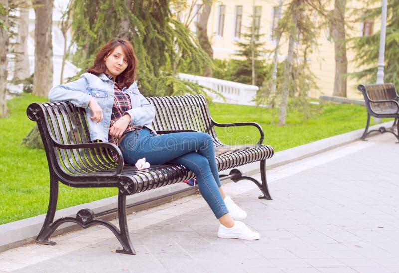 Härlig kvinna som sitter på en bänk royaltyfri foto