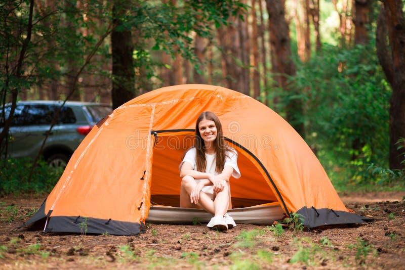Härlig kvinna som sitter utanför tältet i den fria alternativa semestern som campar i den olika livsstilen för skog fotografering för bildbyråer