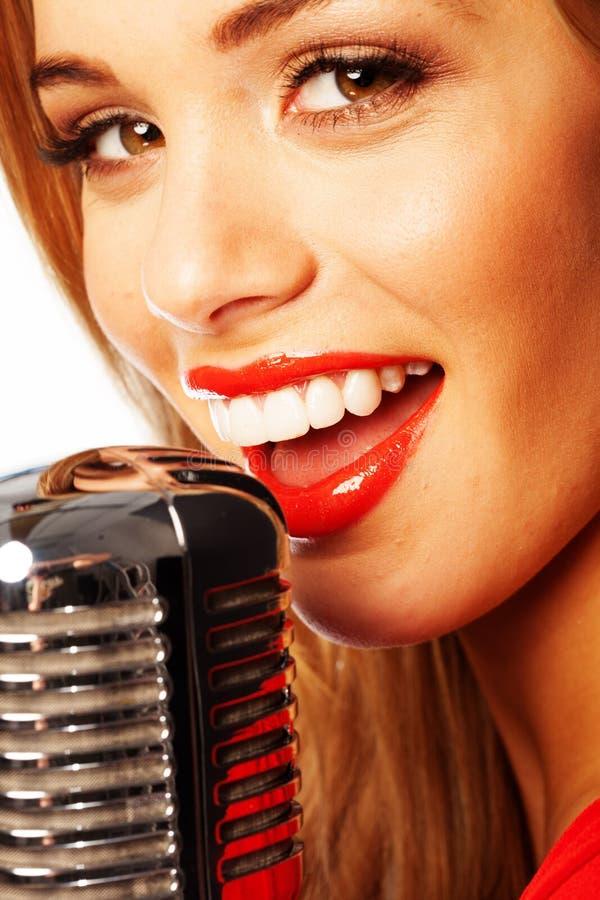 Härlig kvinna som sjunger in i en mikrofon arkivbild