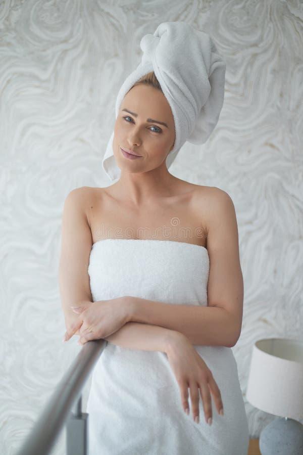 Härlig kvinna som slås in i en ny vit handduk runt om hennes kropp och hår royaltyfri bild