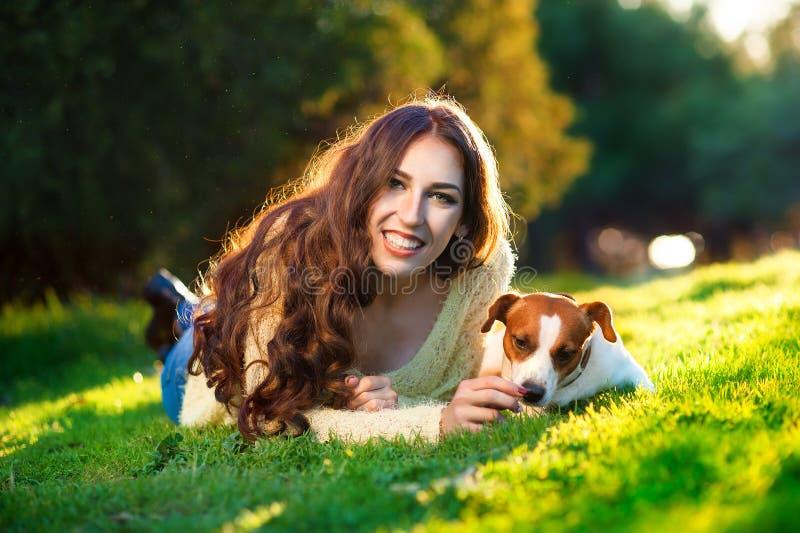 Härlig kvinna som spelar med hennes hund Jack Russell Terrier utomhus- stående serie royaltyfri bild