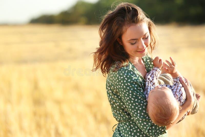 Härlig kvinna som spelar med hennes lilla son i vetefält på sommardag royaltyfri foto