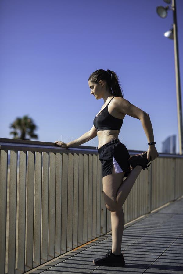 Härlig kvinna som sträcker ben i Barcelona sjösidastrand & x28; SPANIEN royaltyfria foton