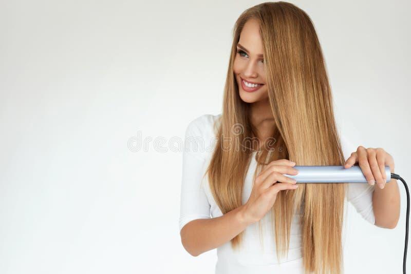 Härlig kvinna som stryker långt rakt hår med straighteneren arkivbilder