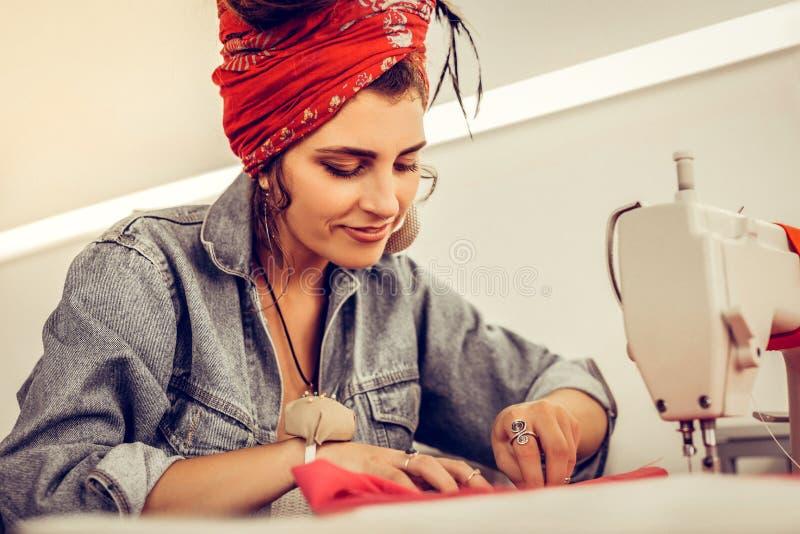 Härlig kvinna som syr en klänning som sitter på skrivbordet arkivfoto