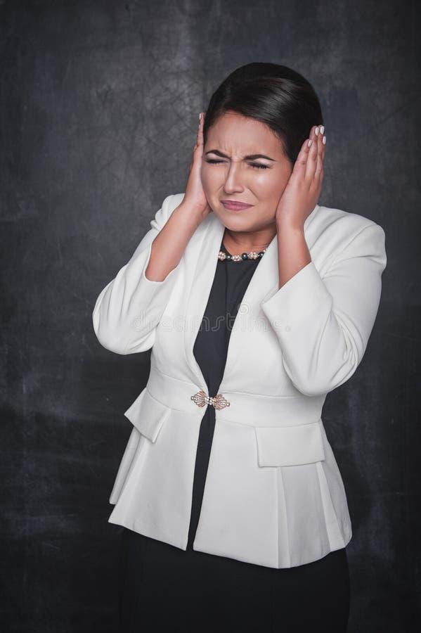 Härlig kvinna som täcker hennes öron vid händer på svart tavla arkivfoto