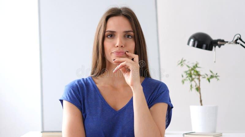 Härlig kvinna som tänker, medan se in camera i regeringsställning fotografering för bildbyråer