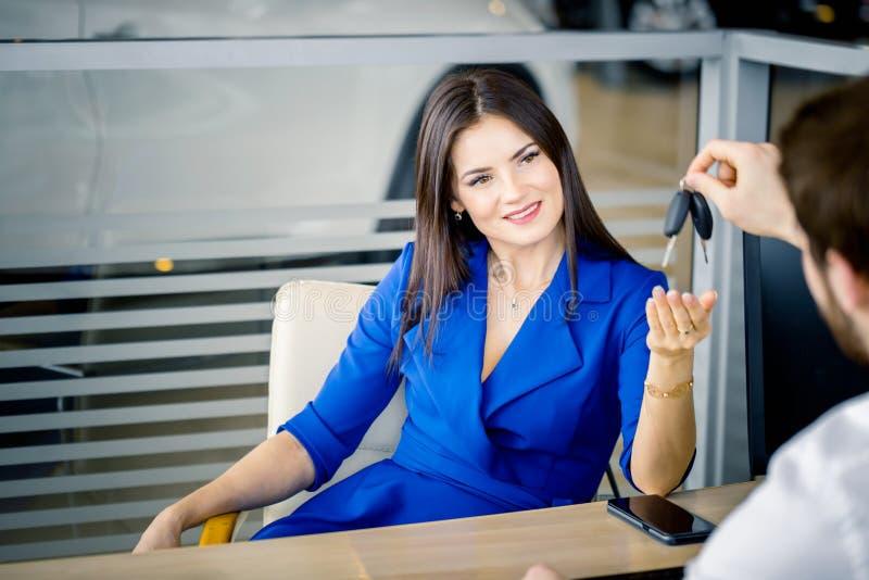Härlig kvinna som tar biltangent från återförsäljare arkivbilder