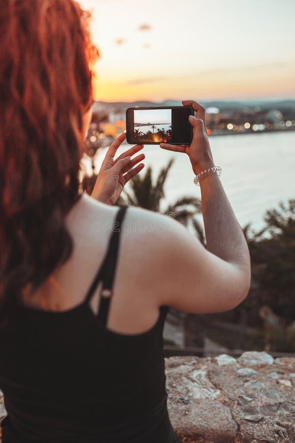 Härlig kvinna som tar ett foto av havslandskapet vid mobiltelefonen i det varma ljuset av solnedgångaftonen royaltyfri bild