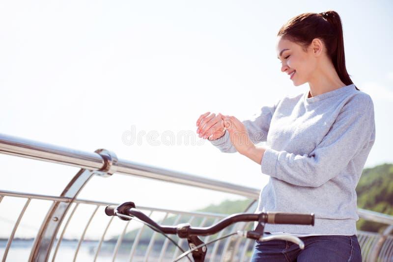 Härlig kvinna som trycker på hennes klocka fotografering för bildbyråer