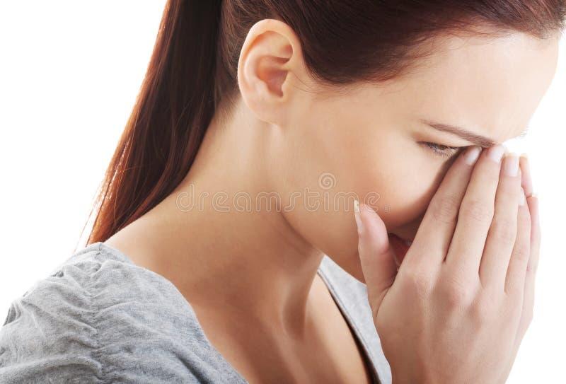 Härlig kvinna som trycker på hennes näsa. arkivbild