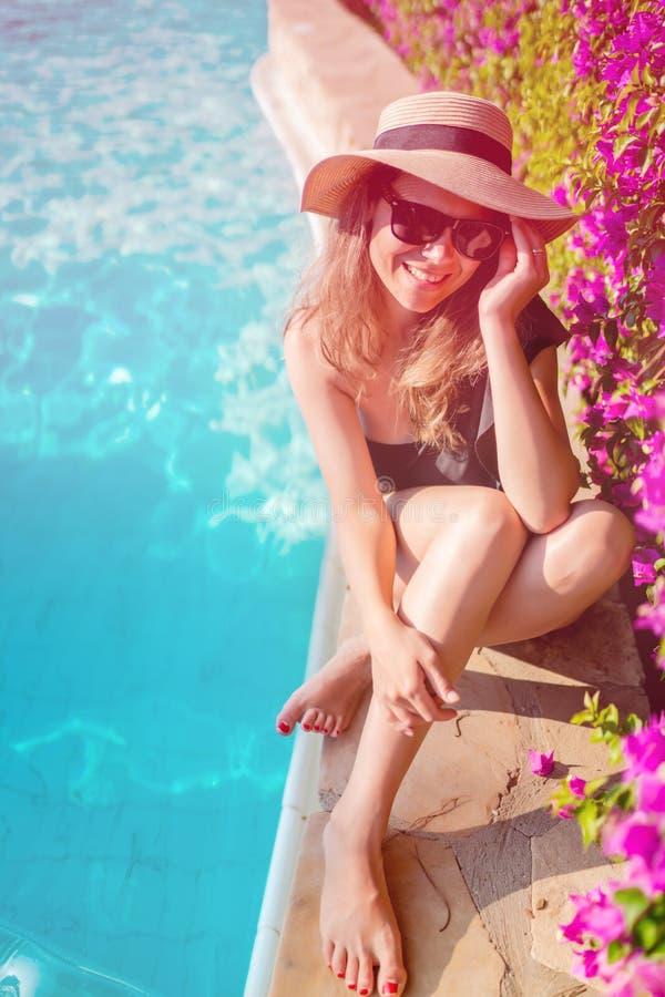 Härlig kvinna som tycker om att solbada vid pölen Sommarbegrepp av den sexiga brunetten latina som lägger på solen på poolsiden royaltyfri foto