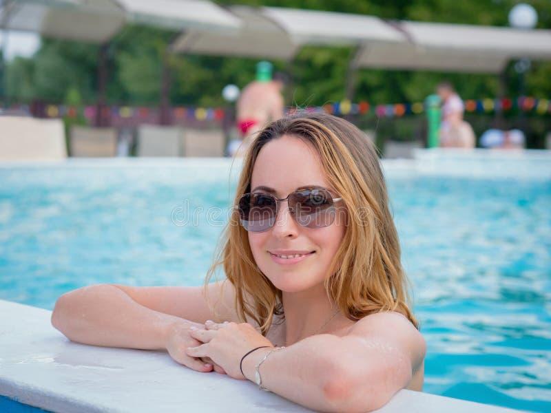 Härlig kvinna som tycker om i simbassäng royaltyfri foto