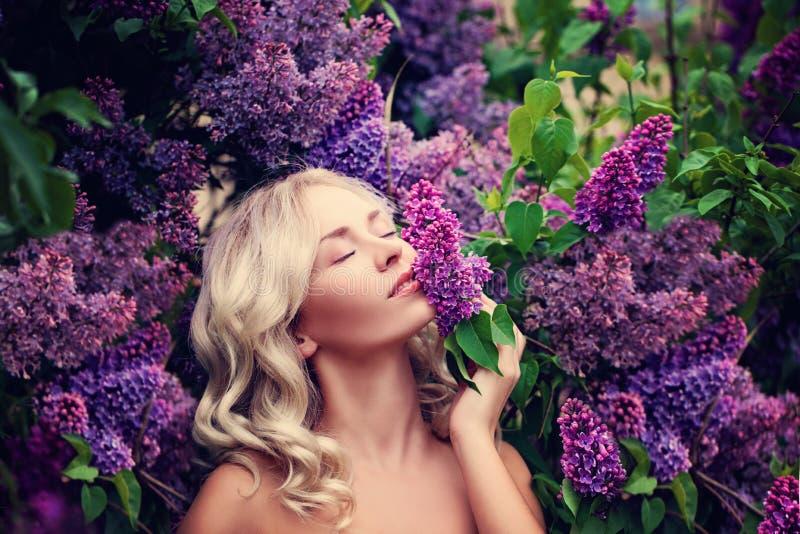 Härlig kvinna som tycker om lukten av lilan royaltyfri fotografi