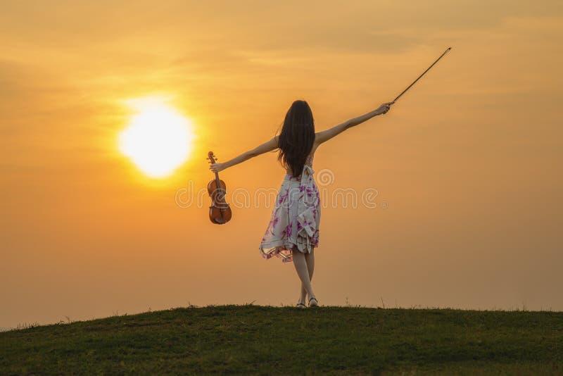 Härlig kvinna som tycker om musik på solnedgången arkivfoton