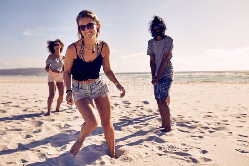 Härlig kvinna som tycker om på stranden med vänner royaltyfri bild