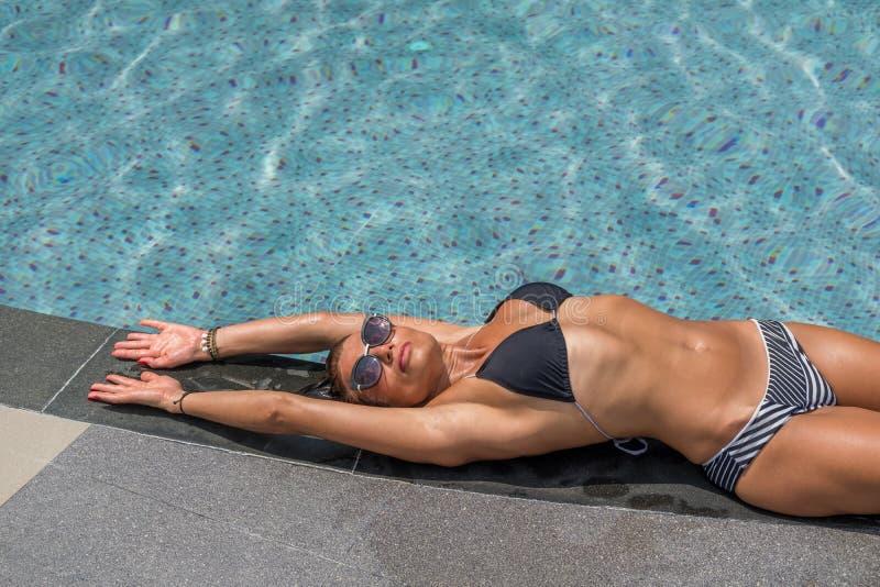 Härlig kvinna som tycker om sommar och garvar att lägga på swimmien royaltyfri fotografi