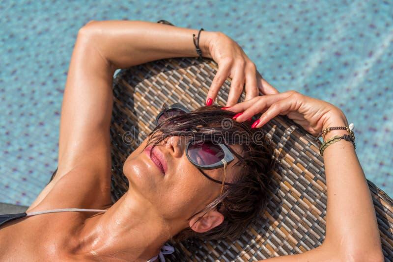 Härlig kvinna som tycker om sommar och garvar på simningbajset fotografering för bildbyråer