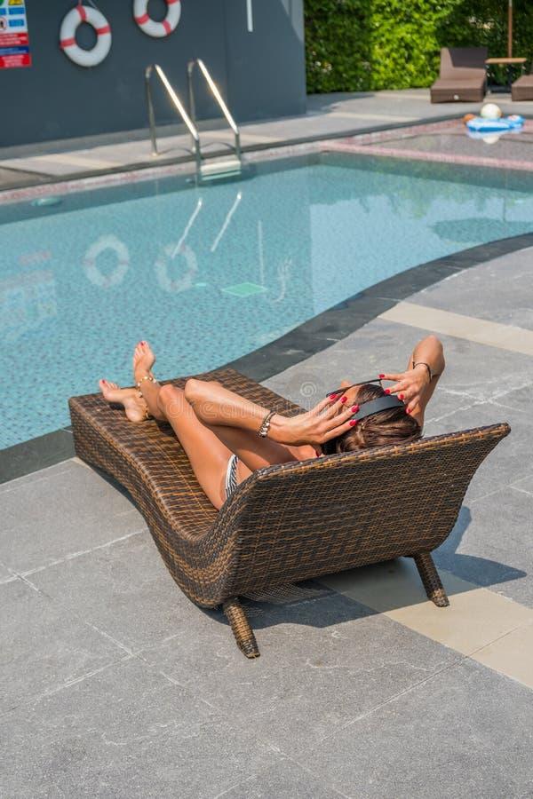 Härlig kvinna som tycker om sommar och lyssnande musik på swimmen royaltyfria bilder