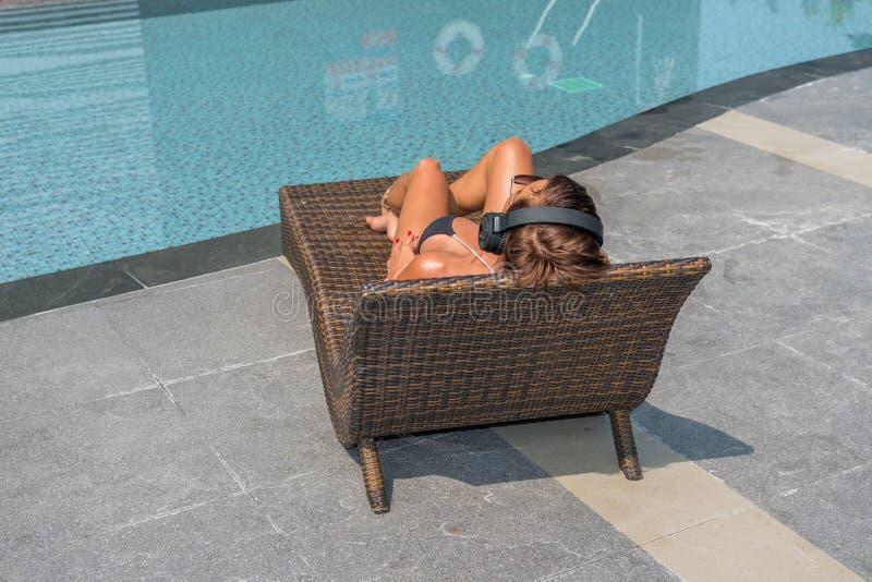 Härlig kvinna som tycker om sommar och lyssnande musik på swimmen fotografering för bildbyråer