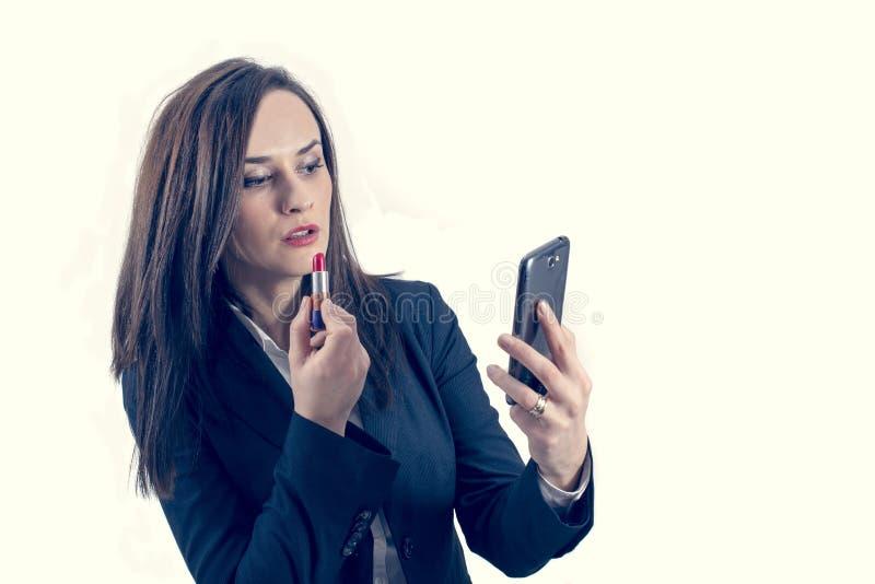 Härlig kvinna som utgör genom att använda hennes telefon som en isolerad spegel royaltyfri bild