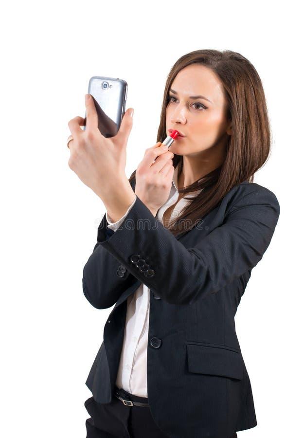 Härlig kvinna som utgör genom att använda hennes telefon som en isolerad spegel arkivbild