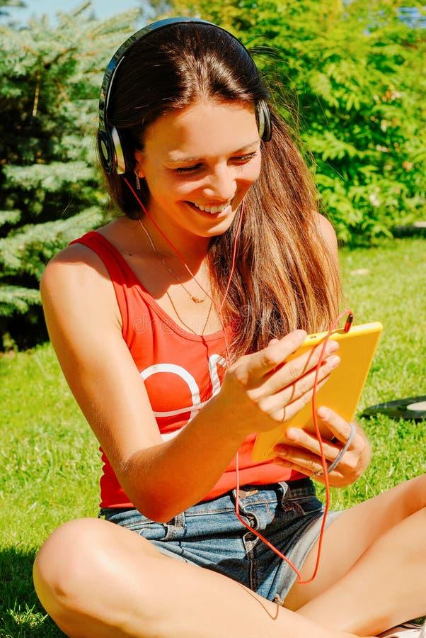 Härlig kvinna som utomhus använder minnestavlan fotografering för bildbyråer