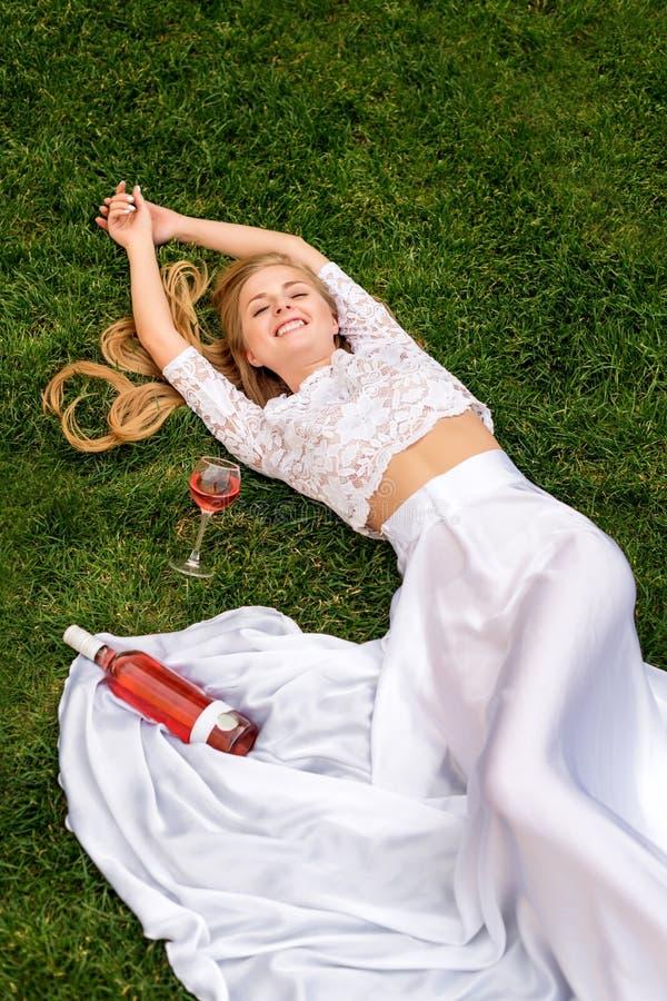 Härlig kvinna som utomhus dricker vin Stående av ung blond skönhet i vingårdarna som har gyckel som tycker om ett exponeringsglas royaltyfria foton