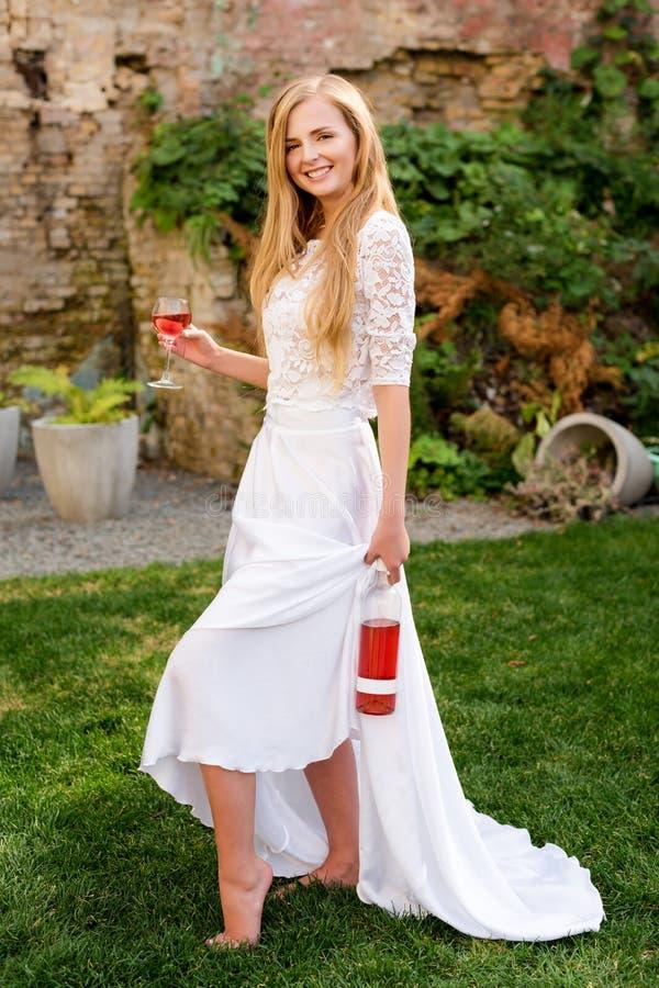 Härlig kvinna som utomhus dricker vin Stående av ung blond skönhet i vingårdarna som har gyckel som tycker om ett exponeringsglas arkivbilder