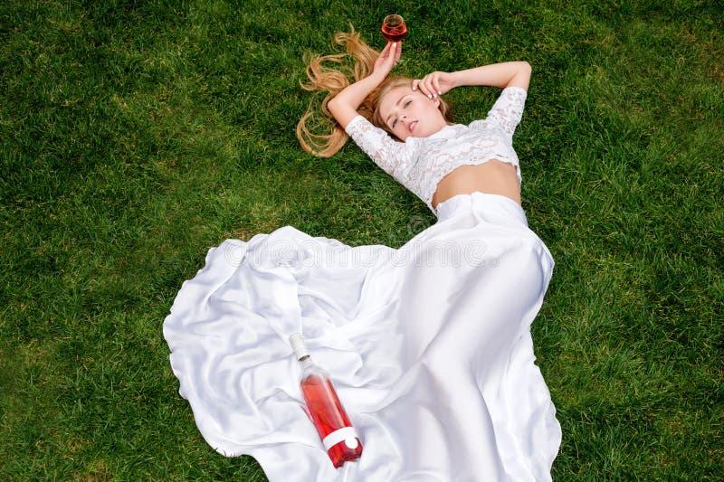 Härlig kvinna som utomhus dricker vin Stående av ung blond skönhet i vingårdarna som har gyckel som tycker om ett exponeringsglas royaltyfri foto