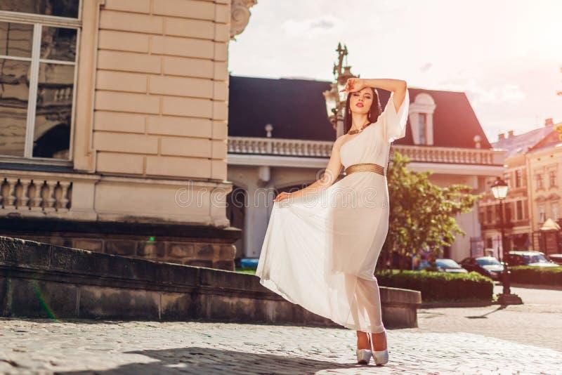 Härlig kvinna som utomhus går i den vita bröllopsklänningen En skuldraklänning med tillbehör och smycken fotografering för bildbyråer