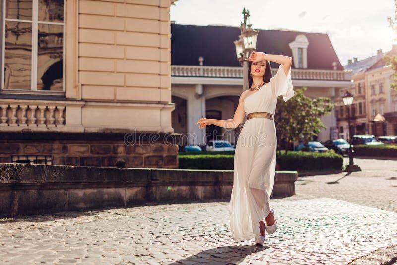 Härlig kvinna som utomhus går i den vita bröllopsklänningen vid den forntida slotten Grekland klänning med smycken och häl arkivbilder
