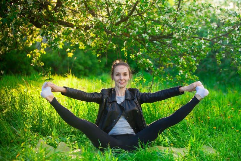 Härlig kvinna som utomhus gör yoga på grönt gräs royaltyfria foton