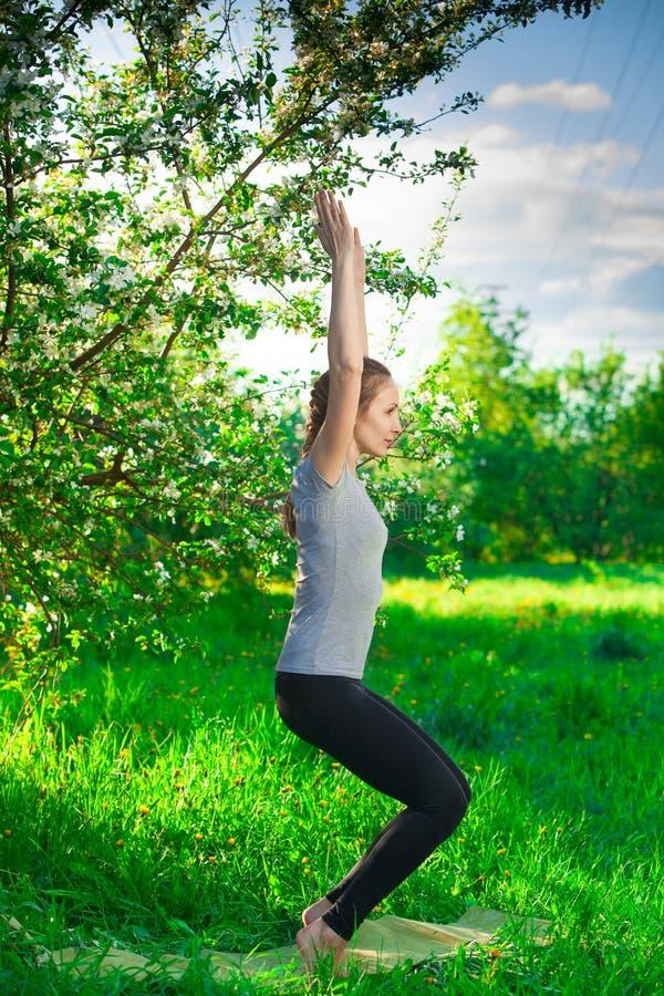 Härlig kvinna som utomhus gör yoga på grönt gräs royaltyfri foto