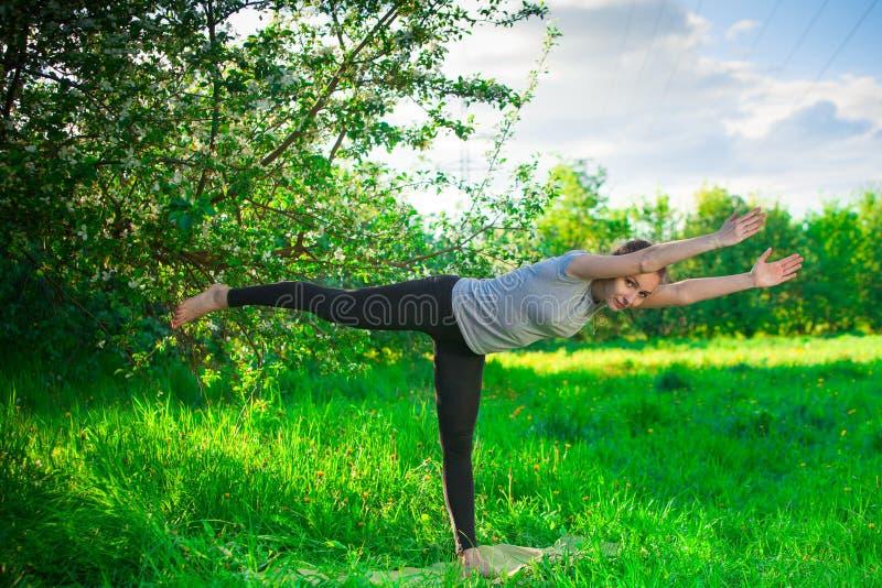 Härlig kvinna som utomhus gör yoga på grönt gräs royaltyfri bild