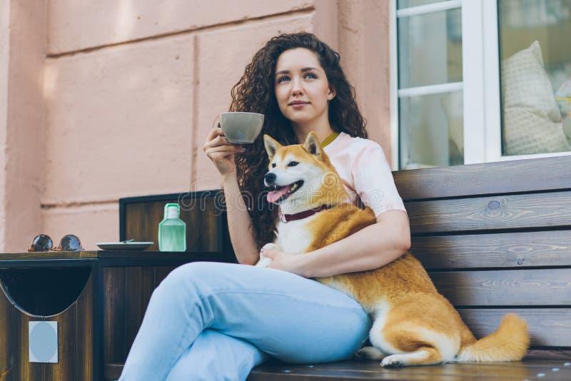 Härlig kvinna som utomhus kopplar av i kafé med den husdjurhunden och koppen kaffe royaltyfri fotografi