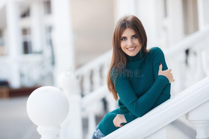 Härlig kvinna som utomhus poserar och att stå på en vit terrass bara royaltyfri bild