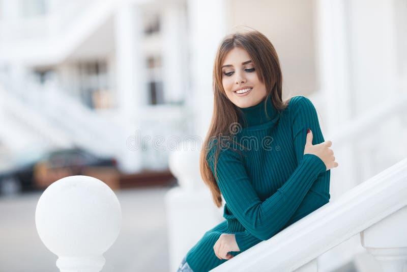 Härlig kvinna som utomhus poserar och att stå på en vit terrass bara royaltyfri foto