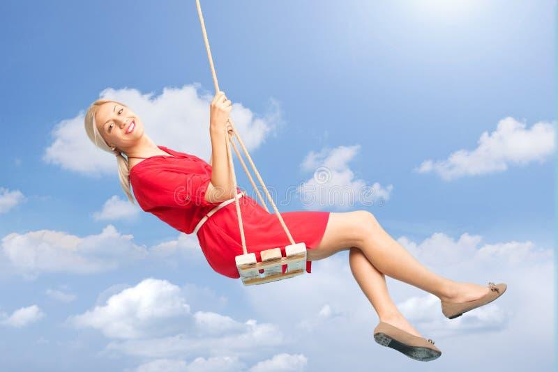 Härlig kvinna som utomhus svänger på en gunga arkivfoto