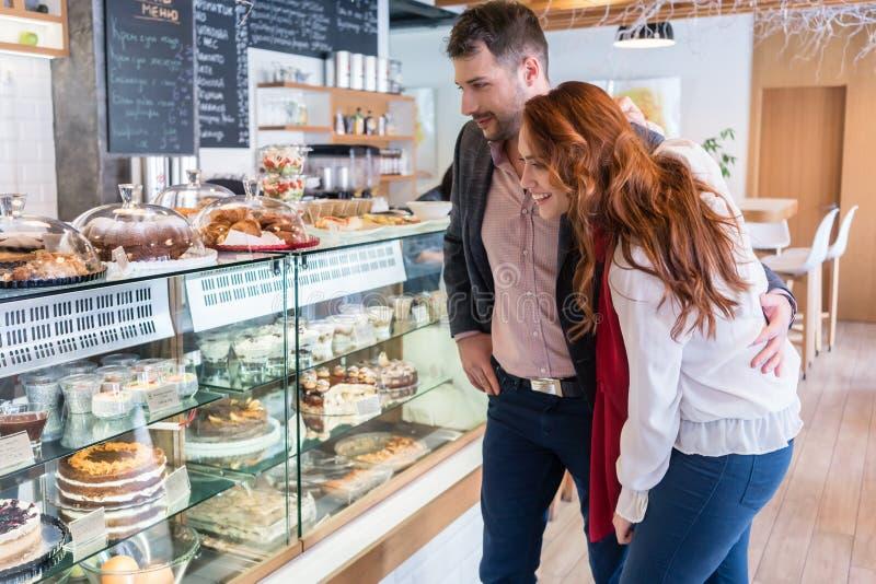 Härlig kvinna som väljer en läcker kaka, medan stå bredvid hennes pojkvän royaltyfri bild