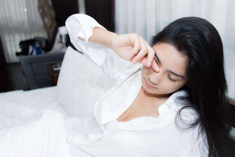 Härlig kvinna som vaknar upp i hennes säng arkivfoton