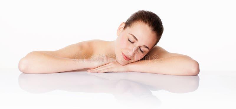 Härlig kvinna som vilar efter att ha rentvått, hydration och rogivande hudbehandling royaltyfri bild