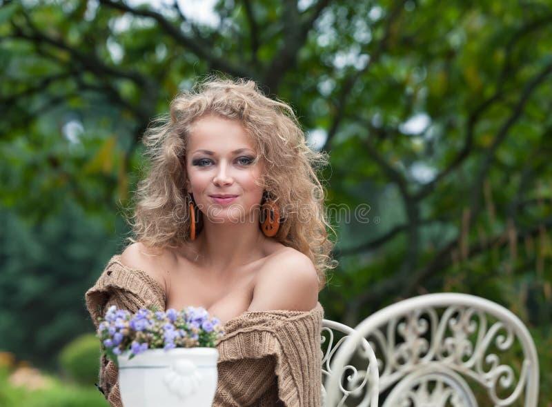 Härlig kvinna som vilar i trädgården royaltyfri foto