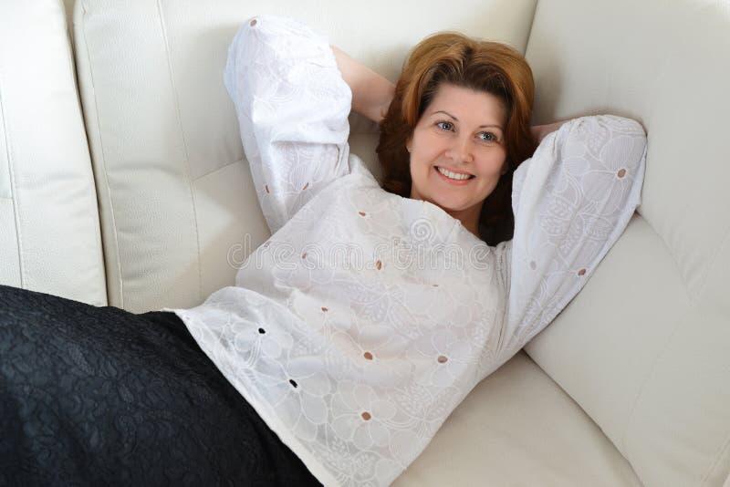 Härlig kvinna som vilar på soffan royaltyfria bilder