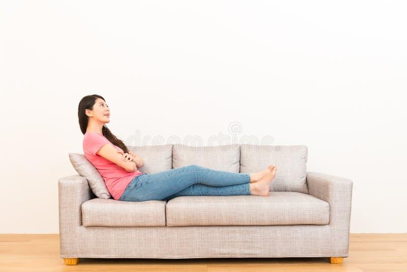 Härlig kvinna som vilar på soffasoffan arkivfoton